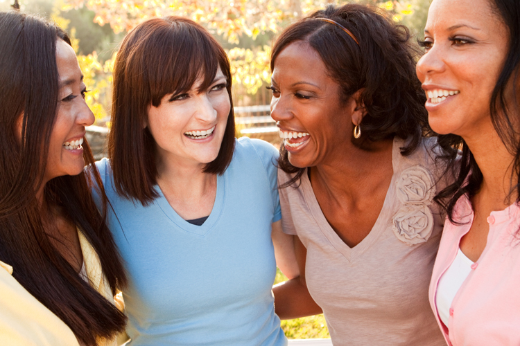 four women laughing together
